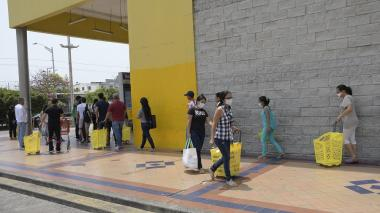 Compradores hacen filas para poder entrar a un supermercado.