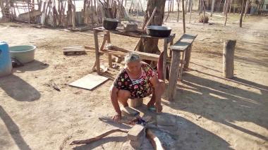 Mujer prepara el fogón de leña.