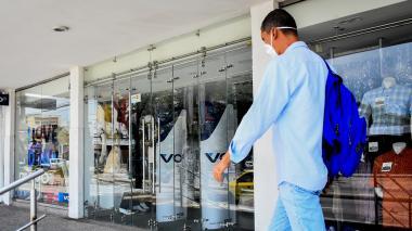 Una persona circulando delante de vitrinas comerciales.