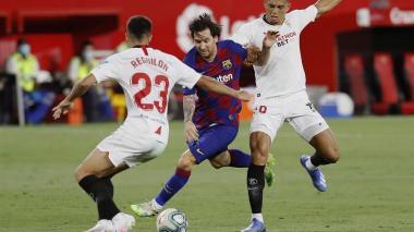 Lionel Messi tratando de eludir a dos defensores del Sevilla.