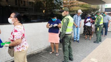 Adultos mayores hacen fila para ingresar a una entidad bancaria.