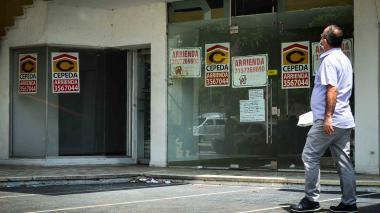Un transeúnte pasa frente a varios locales que se ofrecen en arriendo en la zona norte de Barranquilla.