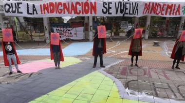 Estudiantes permanecen encadenados mientras sostienen carteles de protesta durante una huelga de hambre en la Universidad Nacional de Colombia.