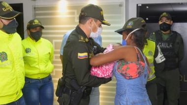 El comandante de la Policía de Cartagena, general Henruy Sanabria, entrega la bebé rescatada a su mamá Emiliainys Rivero.