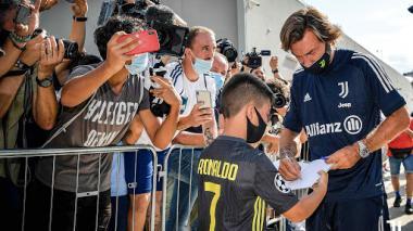 Andrea Pirlo firmando un autógrafo a un pequeño hinhca de la Juventus.