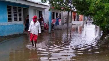 Un hombre camina en medio de una calle inundada tras las fuertes lluvias.