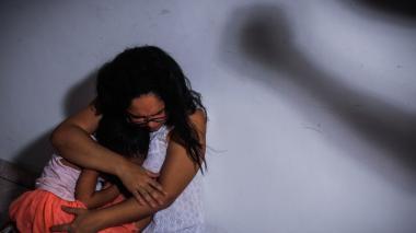 Una mujer protege a una niña de alguien que intenta maltratarla físicamente.