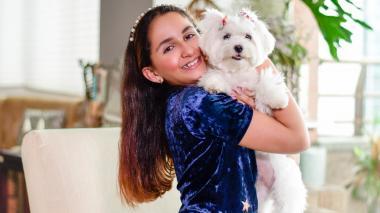 Samia Jadad, de 10 años, posa en su casa con su perrita Luna.