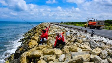 Tres aficionados pescan en el kilómetro 19 de la vía que conduce de Barranquilla hacia Ciénaga. Este será uno de los puntos a intervenir por parte del Invías.