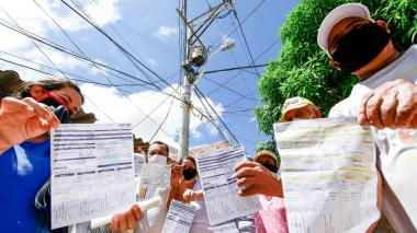 Habitantes del barrio Villa Mar muestran las facturas del mes de octubre.