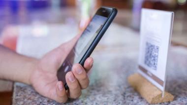 Un hombre acerca su teléfono a un código QR para realizar el pago por una compra.
