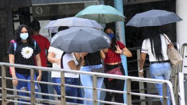 Varias personas se cubren de la lluvia que cayó sobre Barranquilla en la tarde del domingo.