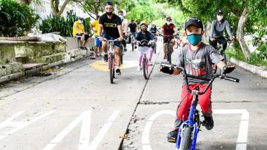 Un grupo niños en bicicletas y patinetas acompañados de adultos.