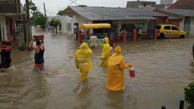 Varios habitantes caminan este sábado por una calle inundada en el barrio Villa Rosa, en Cartagena.