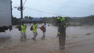 Un policía guía a tres ciudadanos en una zona inundada de Cartagena.
