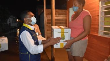 Una mujer damnificada de las inundaciones y deslizamientos de Cartagena recibe un paquete de ayuda alimentaria de manos de funcionario de la UNGRD.