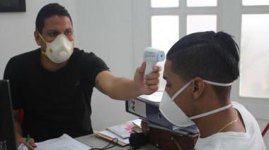 Maikol Ortiz tomándole temperatura a Gabriel Fuentes en cumplimiento de los protocolos de bioseguridad en la sede administrativa del club.