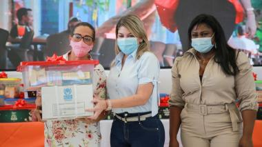 La alcaldesa Virna Johnson entrega una ancheta navideña a una de las lideresas. La acompaña la secretaria de la Mujer, Yunia Palacios.