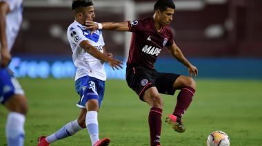 El defensor colombiano Alexis Pérez, de Lanús, disputan el balón con Thiago Almada de Vélez Sarsfield.