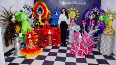 La diseñadora Diana Rolando posa en su taller, rodeada de los maniquíes que lucen las réplicas de los vestidos de coronación de algunas reinas.