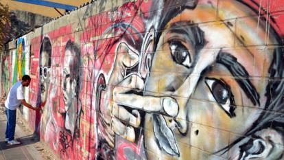 Rafael Matos retoca el grafiti que hace homenaje a tres cantantes de rap barranquilleros, fallecidos en 2012.