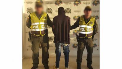 El adolescente aprehendido en medio de dos agentes de la Policía.
