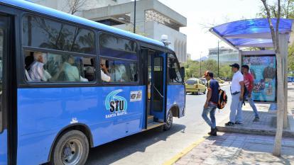 Tres pasajeros abordan un bus urbano en Santa Marta.
