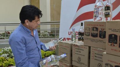 El subsecretario de Rentas del Atlántico, Robinson Pérez, revisa el licor decomisado.