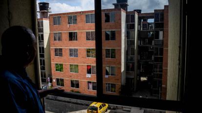 Una persona observa desde la ventana de su apartamento, situado en el cuarto piso de una de las torres del Conjunto 8.