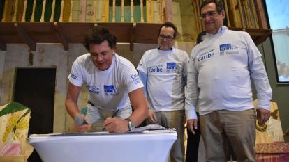 El artista samario Carlos Vives firma el pacto de la Casa Grande al final de la Cumbre por la Inclusión y la Transformación Social. Lo observan el director de EL HERALDO, Marco Schwartz, y el codirector del Banco de la República, Adolfo Meisel.