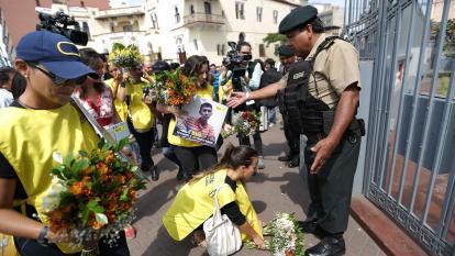 Personas colocan flores en la embajada de Venezuela de Lima como manera de protesta por la corrupción.