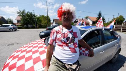 El hincha croata Ivan Pugrar posa frente a su auto decorado con seis banderas, representando simbólicamente las seis victorias del equipo en Sisak.