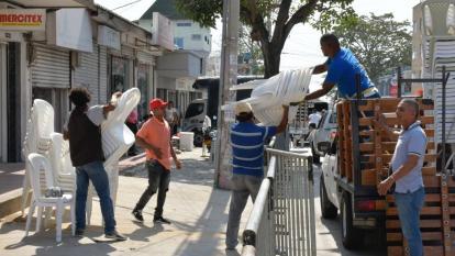 Varios trabajadores acomodan las sillas en la carrera 44, para el desfile de Guacherna.