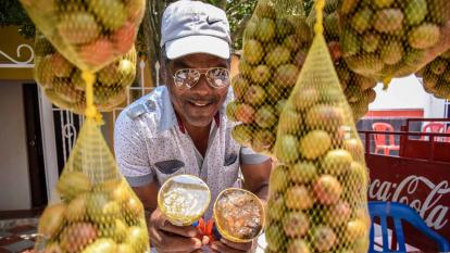 José Fonseca sonríe entre las ciruelas, mientras sostiene algunos de los dulces que preparan sus hijas.