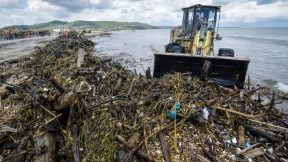 Una pala mecánica amontona basura en playa de Puerto.