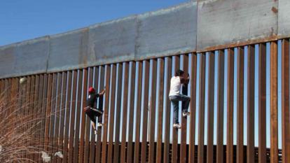 Dos jóvenes escalan el muro a la altura de Ciudad Juárez.