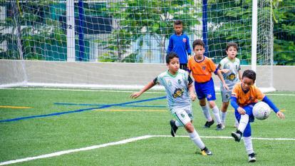 Un grupo de niños juegan un partido de fútbol en la cancha construida en el complejo deportivo.