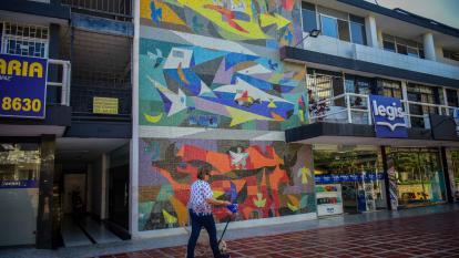 Una mujer pasea con su perro frente al mural 'Tierra, mar y aire' de Obregón.