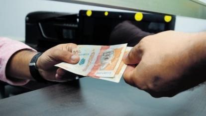 Una persona realiza el pago de seguridad social en una entidad bancaria.