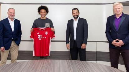 Sané posa con la camiseta del Bayern, junto a los directivos bávaros.