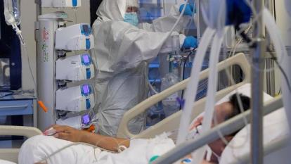 Una enfermera de una unidad de cuidados intensivos (UCI) atiende a un paciente infectado con COVID 19.