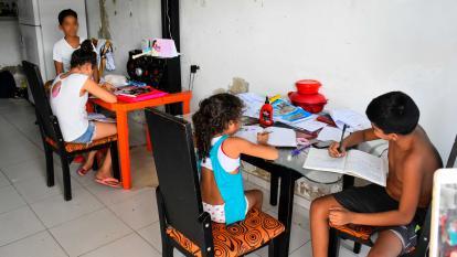 Varios niños realizan sus tareas en una de las viviendas ubicadas en el barrio El Pueblo, en el suroccidente de Barranquilla.