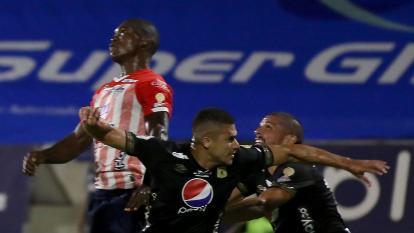 Germán Mera intenta cabecear un balón ante la marca de dos jugadores del América.
