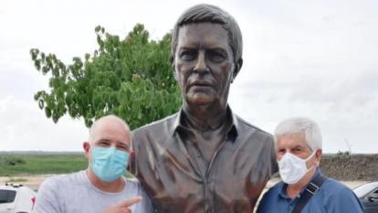 Christian Daes y Julio Comesaña posando junto al busto del entrenador.