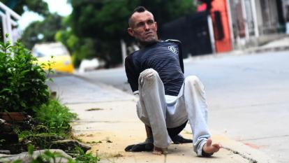 Con guantes y los pies hacia delante, Edgardo se desplaza por su barrio.