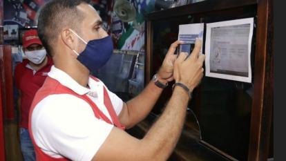 Un funcionario impone el sello a uno de los negocios visitados en los barrios que Cartagena que se mantienen cercados por el aumento de casos de Covid-19.