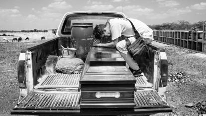 Luis Arévalo, un migrante de Venezuela, se sienta en la parte trasera de una camioneta con el ataúd donde está el cuerpo de su hermana Luisana, en Riohacha.