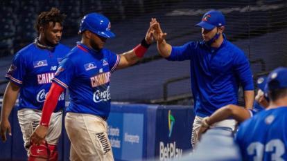 José Mosquera felicita a Harold Ramírez, jardinero, en su llegada al dugout tras anotar una carrera.
