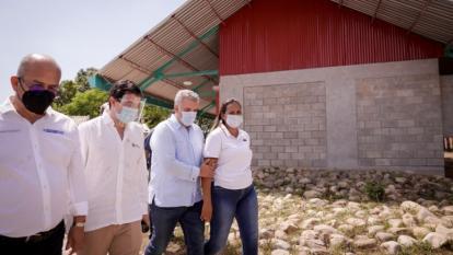 El presidente Iván Duque camina junto a Gina Ruiz, una habitante de Puerto Patiño. Aparecen además el contralor General, Felipe Córdoba, y el director del Fondo Adaptación, Édgar Ortiz.