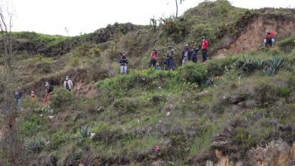 Migrantes venezolanos observan hoy desde una de las colinas junto al cauce del fronterizo río Carchi, mientras esperan que se disperse una operación conjunta militar entre Ecuador y Colombia.